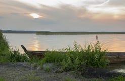 Fartyg i en sjö på solnedgången Royaltyfria Bilder