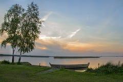 Fartyg i en sjö på solnedgången Arkivfoton