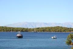 Fartyg i fjärden med ett berg i bakgrunden Arkivfoto