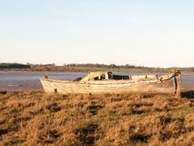 Fartyg i gyttjan med tidvattnet ut Arkivbilder