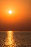 Fartyg i solnedgången i havet med reflexioner och moln royaltyfri fotografi