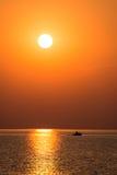 Fartyg i solnedgången i havet med reflexioner och moln royaltyfria bilder