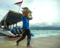 Fartyg levererar 24/7 all sort av material att kompensera bristen av resurser av ön Här besättningen som lastar av ris arkivbilder