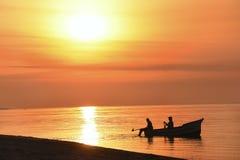 Fartyg med fiskare i havet på soluppgång, solnedgång härlig färgrik himmel och vatten med reflexionen av ljus Konturer av f Royaltyfri Foto