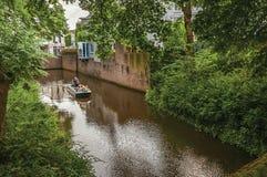 Fartyg med folk som navigerar kanalen som omges av väggar och frodig vegetation i s-Hertogenbosch Arkivfoton