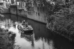 Fartyg med folk som navigerar kanalen som omges av väggar och frodig vegetation i s-Hertogenbosch Arkivfoto