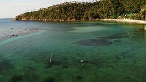Fartyg nära kust av ön Traditionella färgrika fiska skyttlar som svävar på lugna blått vatten nära den vita sandkusten av stock video