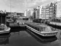 Fartyg och byggnader på den Amsterdam kanalen i svartvitt Royaltyfri Bild
