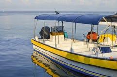 Fartyg och dess reflexion på pir av den lilla Garifuna staden av Livingston, det karibiska havet, Guatemala Royaltyfri Foto