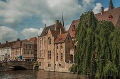 Fartyg och gamla byggnader på kanal`en s kantar på Bruges Royaltyfri Bild
