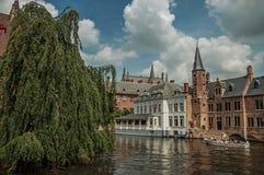 Fartyg och gamla byggnader på kanal`en s kantar på Bruges Royaltyfri Foto