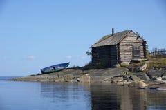 Fartyg och gammal koja på stenig sjökust Arkivfoto