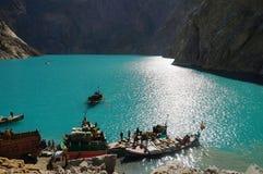 Fartyg och lastbilar på Attabad sjön i nordliga Pakistan Arkivbild