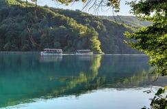 Fartyg och reflexioner på sjön mellan bergen Arkivbilder