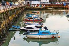 Fartyg och skepp förtöjde i en liten port, i bakgrundsstenen Arkivfoton
