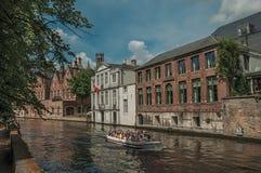Fartyg- och tegelstenbyggnader på kanal`en s kantar på Bruges Arkivfoton