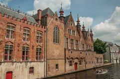 Fartyg- och tegelstenbyggnader på kanal`en s kantar på Bruges Arkivbilder