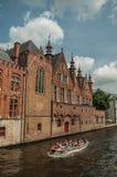 Fartyg- och tegelstenbyggnader på kanal`en s kantar på Bruges Royaltyfri Foto