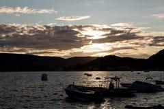 Fartyg och yachter anslöt på pir i fjärden av Montenegro på solnedgången och berg Arkivbilder