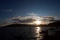 Fartyg och yachter anslöt på pir i fjärden av Montenegro på solnedgången och berg Fotografering för Bildbyråer