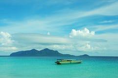 Fartyg på en havskust med en ö vid bakgrunden Royaltyfria Bilder