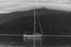 Fartyg på en sjö med bergbakgrunden Arkivfoton