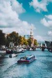 Fartyg på floden Amstel i landskap för stad för Amsterdam Nederländernagränsmärke gammalt europeiskt Pittoresk cloudscape royaltyfri fotografi