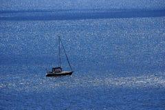 Fartyg på havet En ensam segelbåt i det blåa havet Royaltyfria Foton
