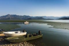 Fartyg på kusten av Shkoder sjön som omges av berg, Montenegro arkivbild