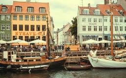 Fartyg på pir av dansk huvudstad med historiska byggnader på populärt Nyhavn område fotografering för bildbyråer