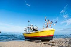 Fartyg på sandstranden i Gdansk, Polen Litet skepp på havskust på blå himmel Skyttel- och vattentransport för sommarterritorium f arkivbild