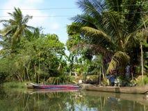 Fartyg på sidan en vattenväg i den Mekong River deltan Arkivfoton