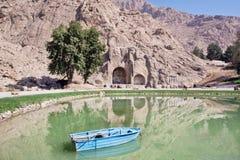 Fartyg på sjön av berg med forntida bågar av Taq-e Bostan Royaltyfria Foton