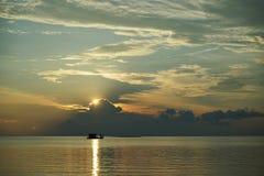 Fartyg på solnedgången och soluppgång med dramatisk himmel över havet royaltyfri fotografi