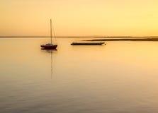 Fartyg på solnedgången på en flod Royaltyfri Bild