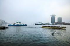 Fartyg på stad kanaliserar nära pir av centralstationen i dimmig dag Arkivbilder