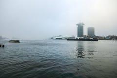 Fartyg på stad kanaliserar nära pir av centralstationen i dimmig dag Arkivfoton
