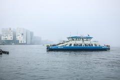 Fartyg på stad kanaliserar nära pir av centralstationen i dimmig dag Arkivfoto