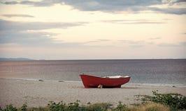Fartyg på stranden Fishermens fartyg på seacoasten, på sand på molnig dag med havet på bakgrund Fiskebåt på stranden in Arkivfoton