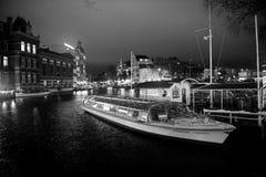 Fartyg på vattenkanalen och byggnader vid natt i Amsterdam Arkivbilder
