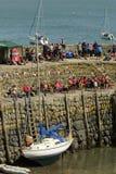 Fartyg som är aground, och tittare på hamnskyddsmur mot havet på Clovelly, Devon Royaltyfria Foton
