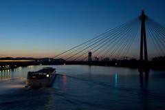 fartyg som är rörande på flod- och drevpasserande över bron, Wien Arkivbild