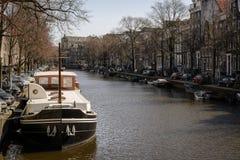 Fartyg som förtöjas i en kanal i Amsterdam Nederländerna Mars 2015 arkivfoto