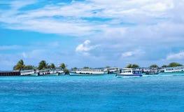Fartyg som förtöjas på den manliga hamnen, Maldive ö på en solig blå clou Arkivfoto