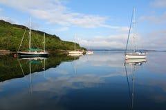 Fartyg som förtöjer på ett fridsamt hav Fotografering för Bildbyråer