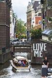 Fartyg som går till och med den smala kanalen i Amsterdam royaltyfria bilder