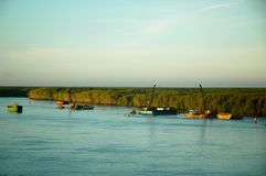 Fartyg som muddrar en flod i Vietnam, är luminiscenta i soluppgången Royaltyfria Foton
