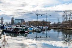 Fartyg som parkeras på marina i Northampton med bakgrund för konstruktionskranar Arkivfoto