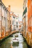 Fartyg som seglar i vattenkanal med orange byggnader Royaltyfria Bilder