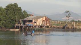 Fartyg som svävar på floden nära huset på styltor Två fiskare sitter i fartyget stock video